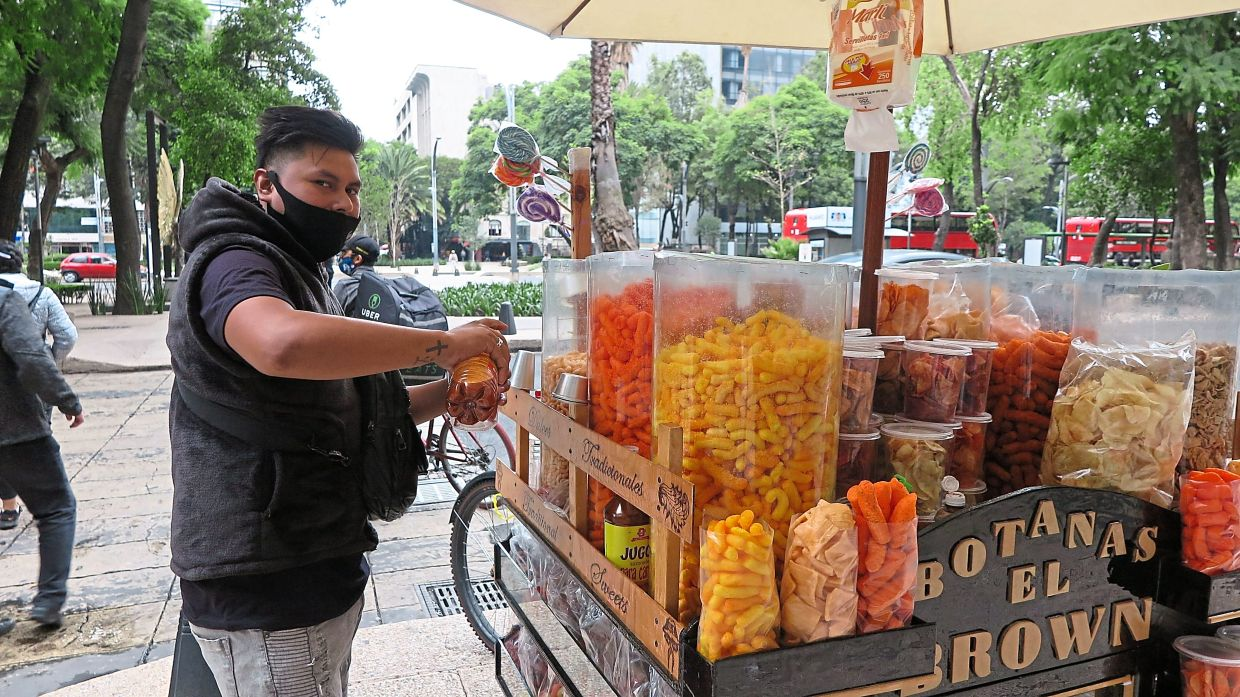 Jonathan Mateos Chalchi preparing a snack for a customer at his cart in Mexico City. 'It's a question of not eating it excessively,' he says. — dpa