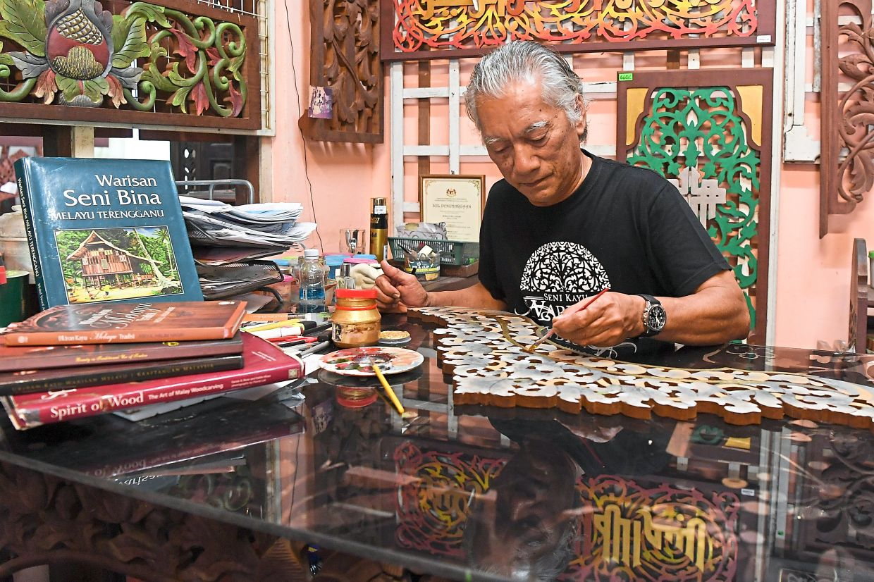 Burhan uses fruit essence and herbs such as 'pinang' (areca nuts) and turmeric to create yellow colour, 'bunga senduduk' (melastoma) (purple) and mangosteen peel (red). Photo: Bernama