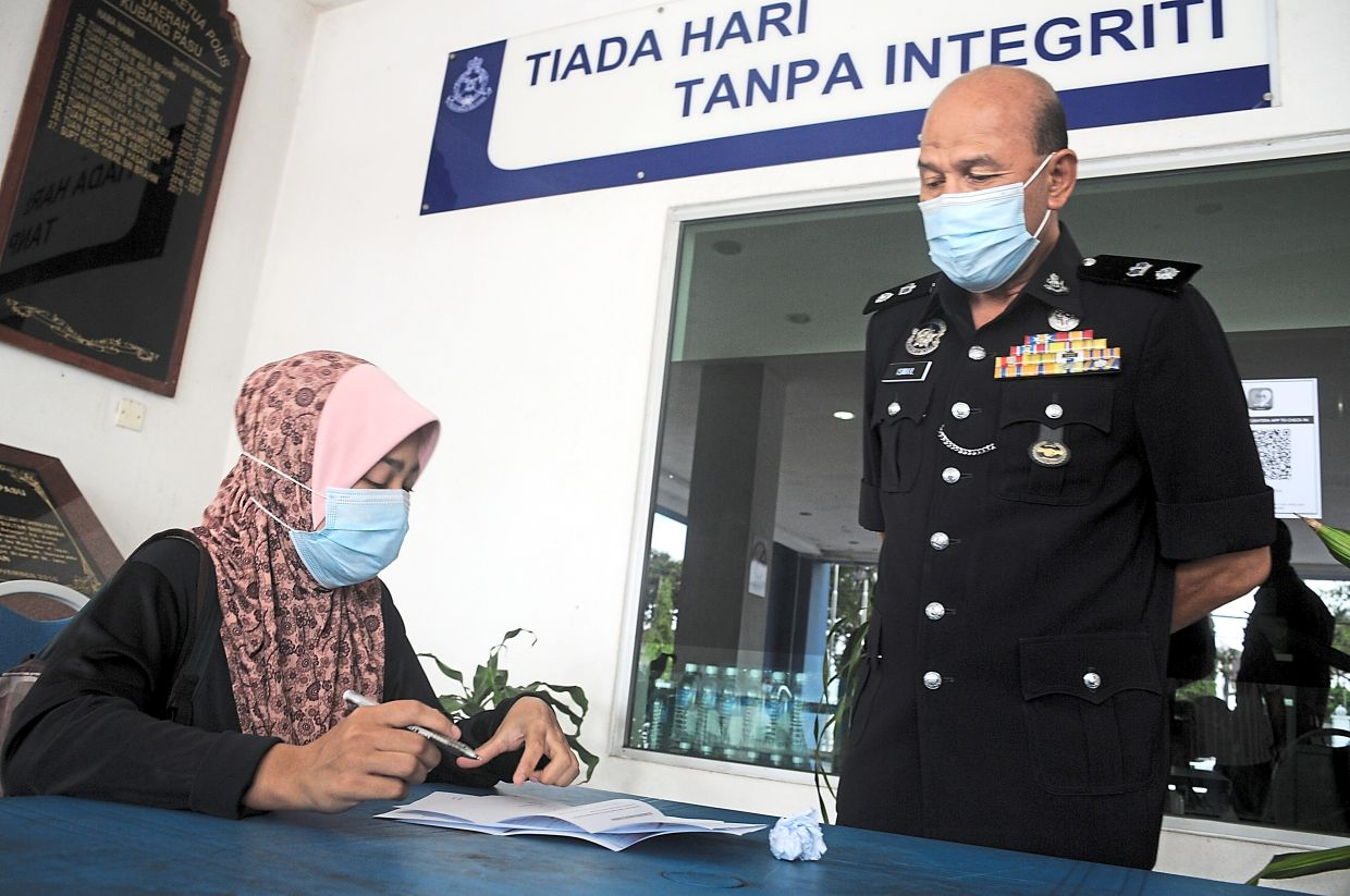 Supt Mohd Ismail observing a woman filling up the consent application form to seek permission to travel out of the district at the Kubang Pasu district police headquarters in Kedah.