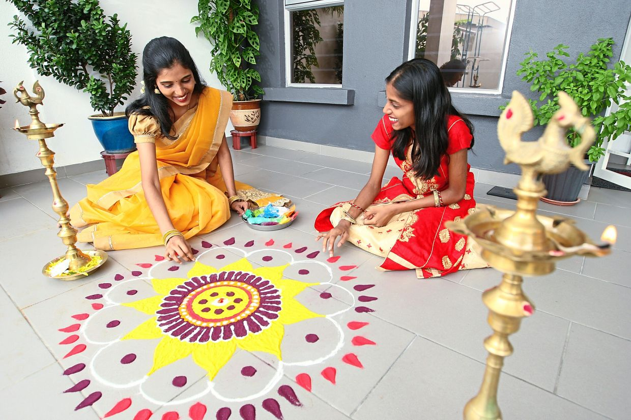 Daughters (from left) Kayal Vili and Kanimolhi preparing the Kolam traditional art at the entrance of the home. Photo: The Star/Azman Ghani