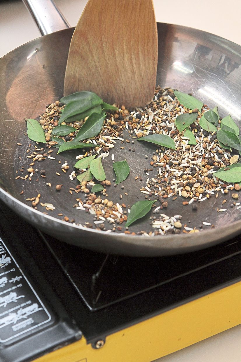Slowly roast the ingredients for the masala until the spices turn fragrant and the mustard seeds start to pop.