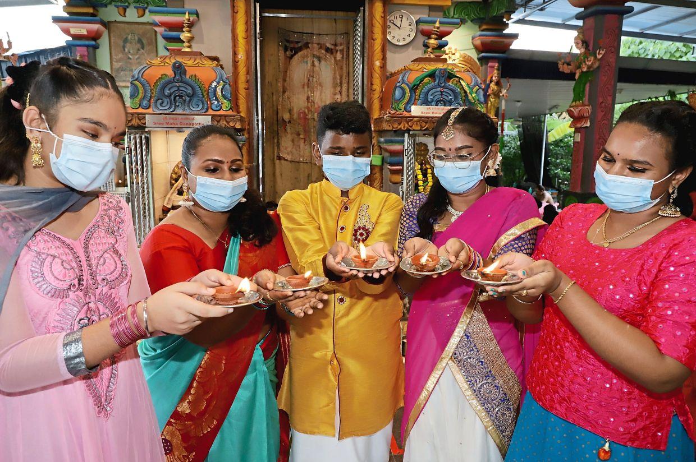 (From left) Friends Reshmaljeet Kaur Hardip Singh, 12, Dishaalini Ganesan, 24, Sharveshvaaran Ganesan, 13, Pavithra Surresh Kumar, 21, and Nivaashini Ganesan, 15, lighting up the oil lamps during the Deepavali celebration at Arulmigu Sree Veeramuthu Maha Mariamman Temple in Bayan Lepas, Penang. — Photo: LIM BENG TATT/The Star