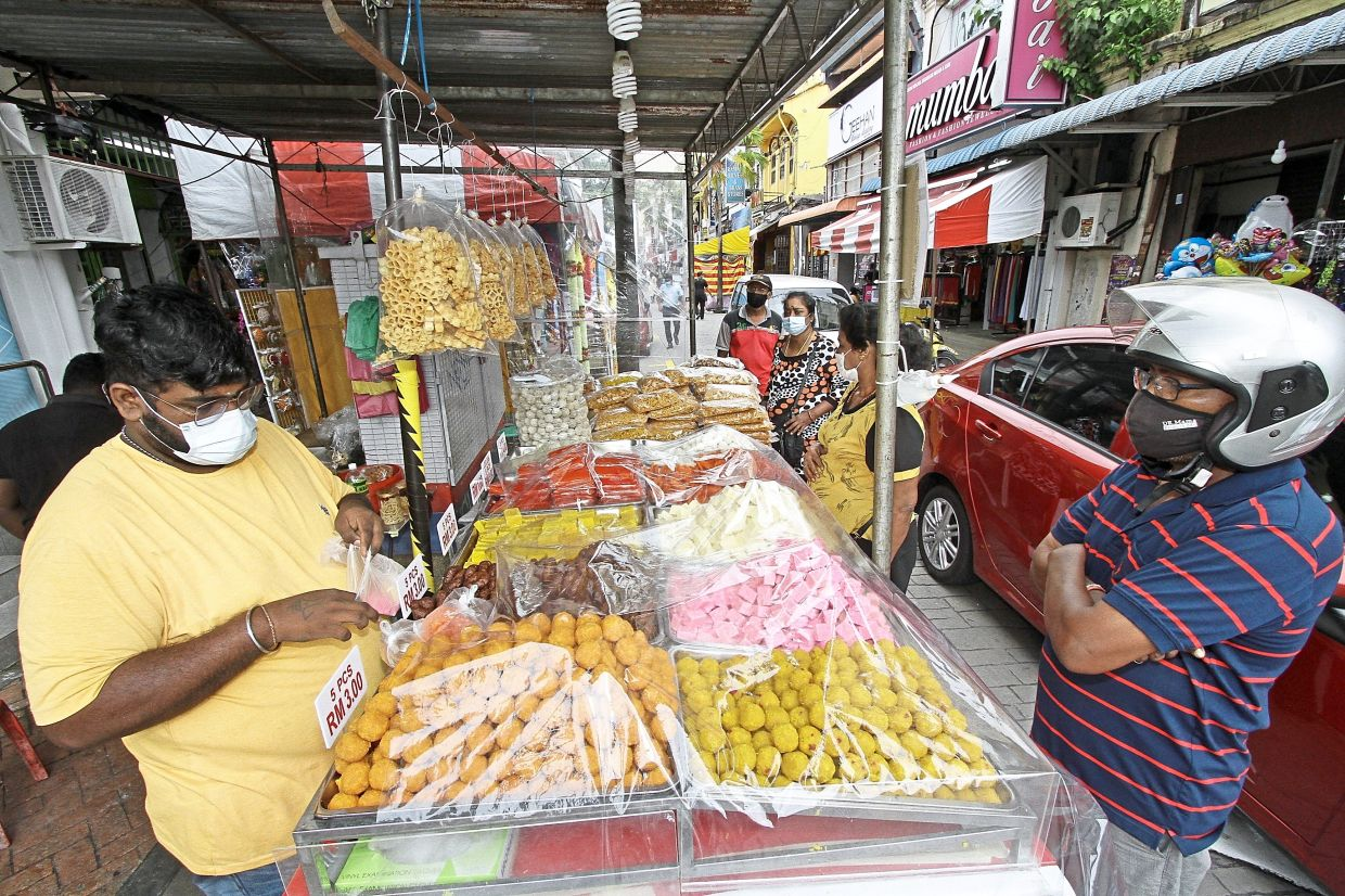 A shopper getting Indian sweets from a stall in Little India.