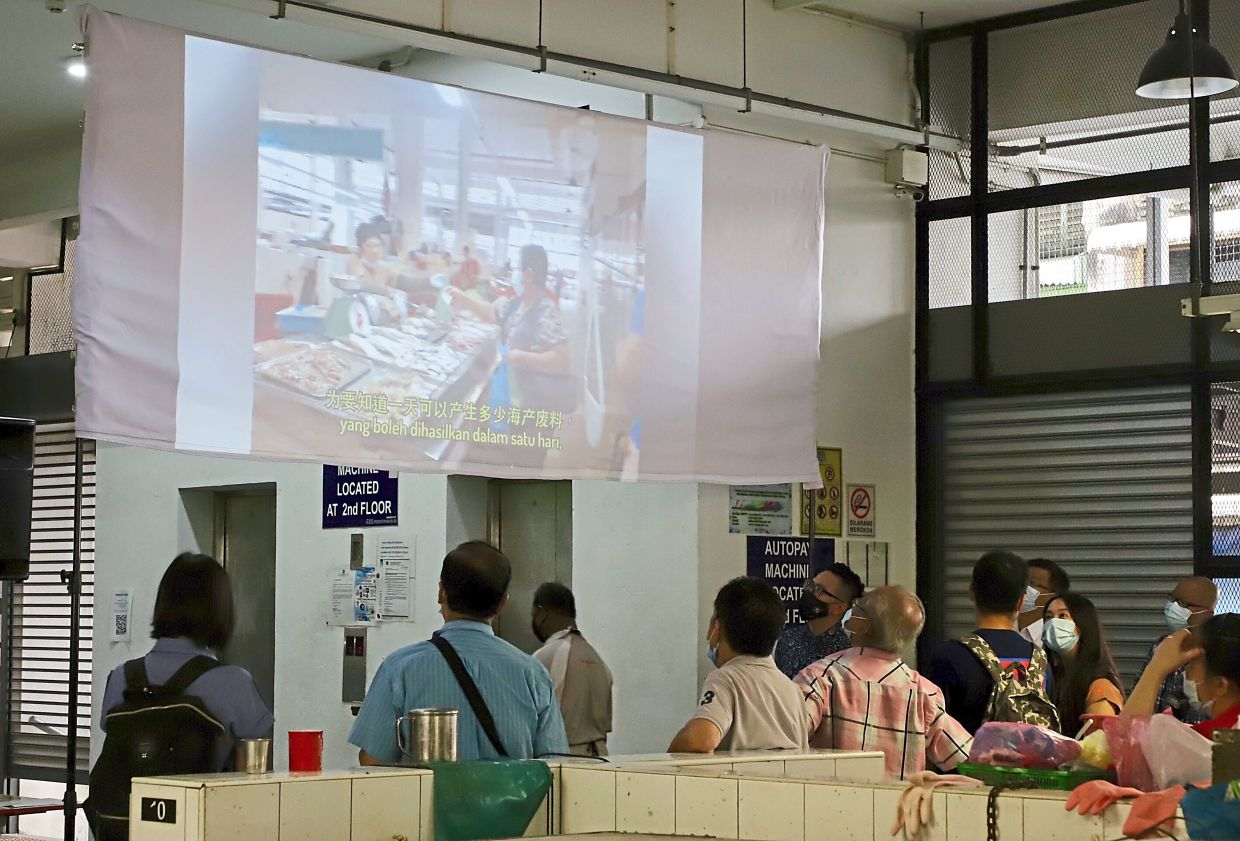 Visitors at Chowrasta Market watching a video during the event.