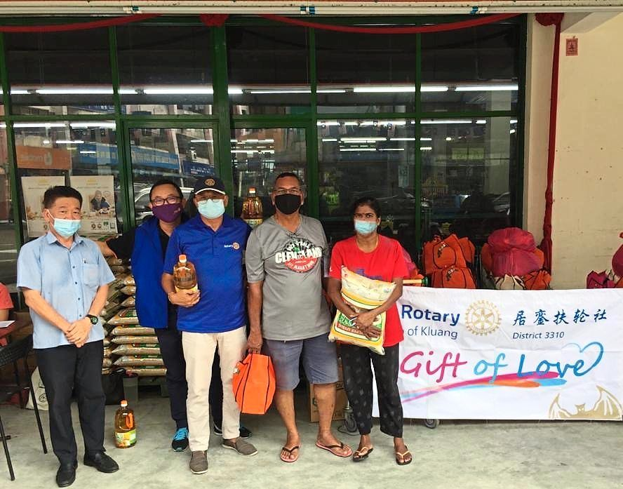 Rotary Club of Kluang members presenting food aid to some recipients in conjunction with Deepavali.