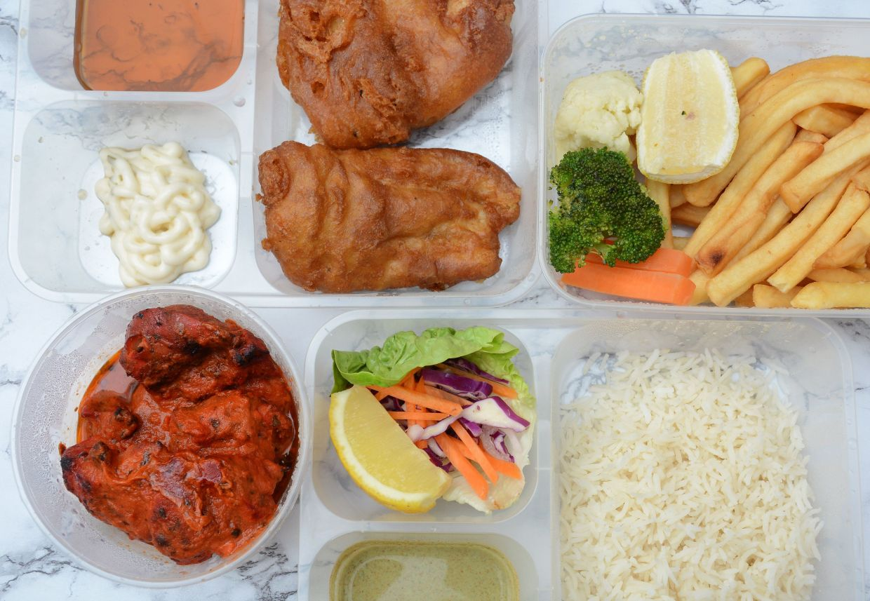 The takeaway items come neatly packed in containers. Shown here are the Rasa Fish and Chips (top) and Butter Chicken (bottom).
