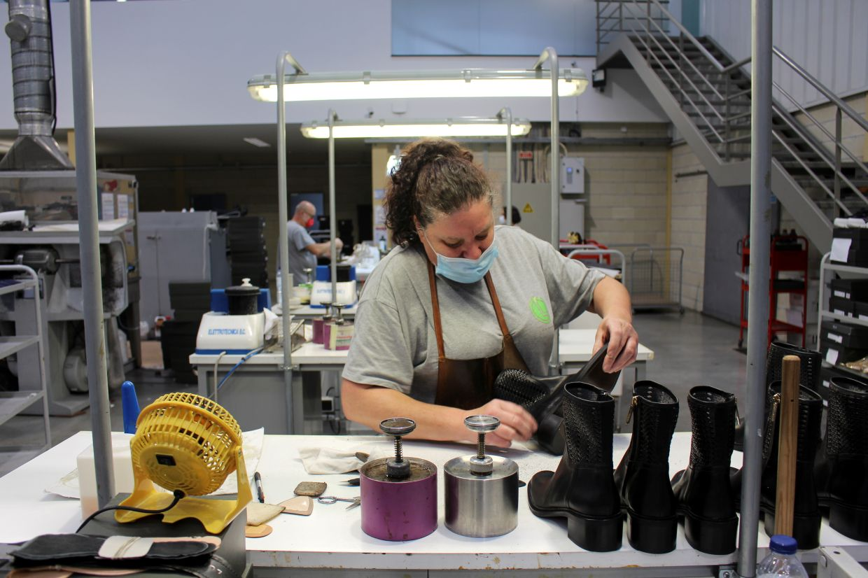 A worker gives a final touch to a boot at a factory owned by luxury shoe designer Luis Onofre. Photo: Reuters