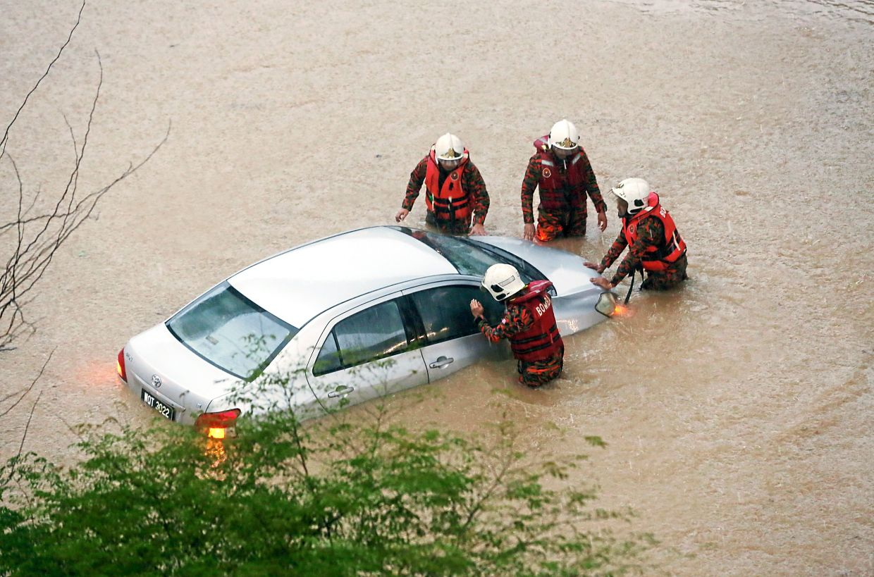 Kuala Lumpur has experienced numerous severe floods in recent times. In this flash flood on Sept 2, firefighters are trying to help the driver of this car that is stuck in waist-high waters near the Taman Mutiara MRT station. — Filepic