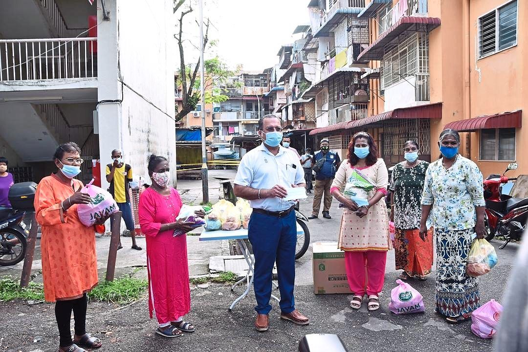 Jagdeep (centre) handing over food items and face masks to needy residents at Taman Free School.