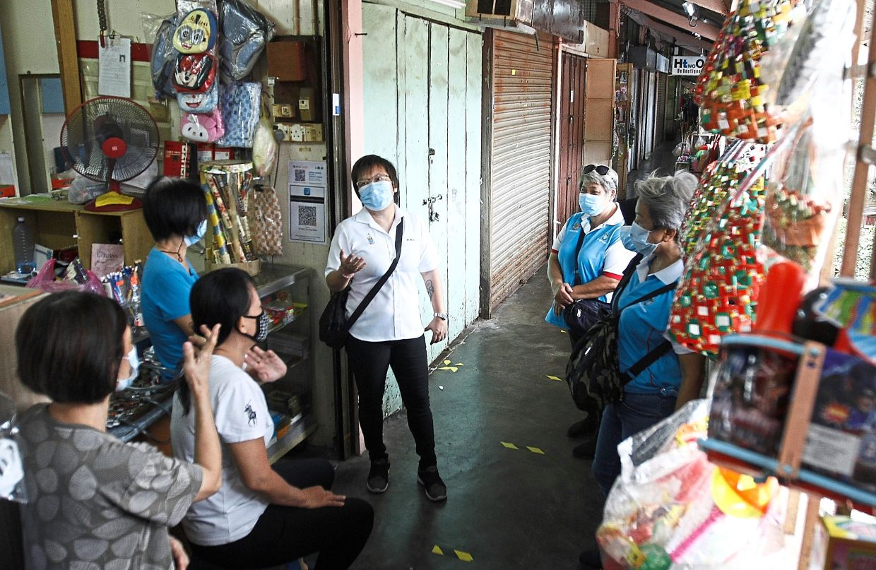 Jin (centre) chatting with traders while on a walkabout to advise the public about SOP compliance at the Rifle Range food court in Ayer Itam.
