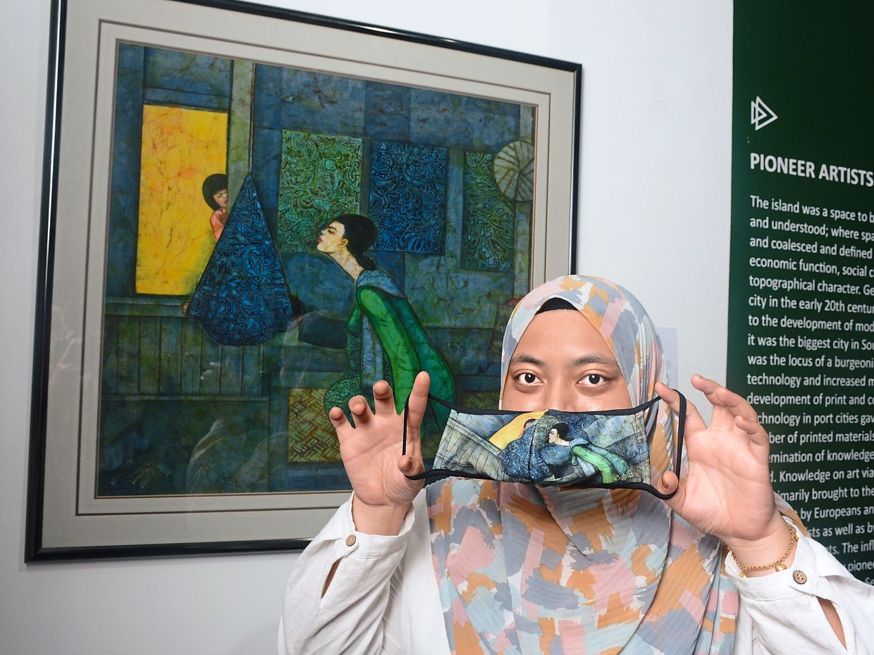 A Penang State Art Gallery staff member holding up one of the masks based on Chuah's 1995 batik painting titled 'Lullaby' while another (below) shows off one of the face mask designs inspired by the late Syed Ahmad's 1995 acrylic work 'Hujan Rahmat'.
