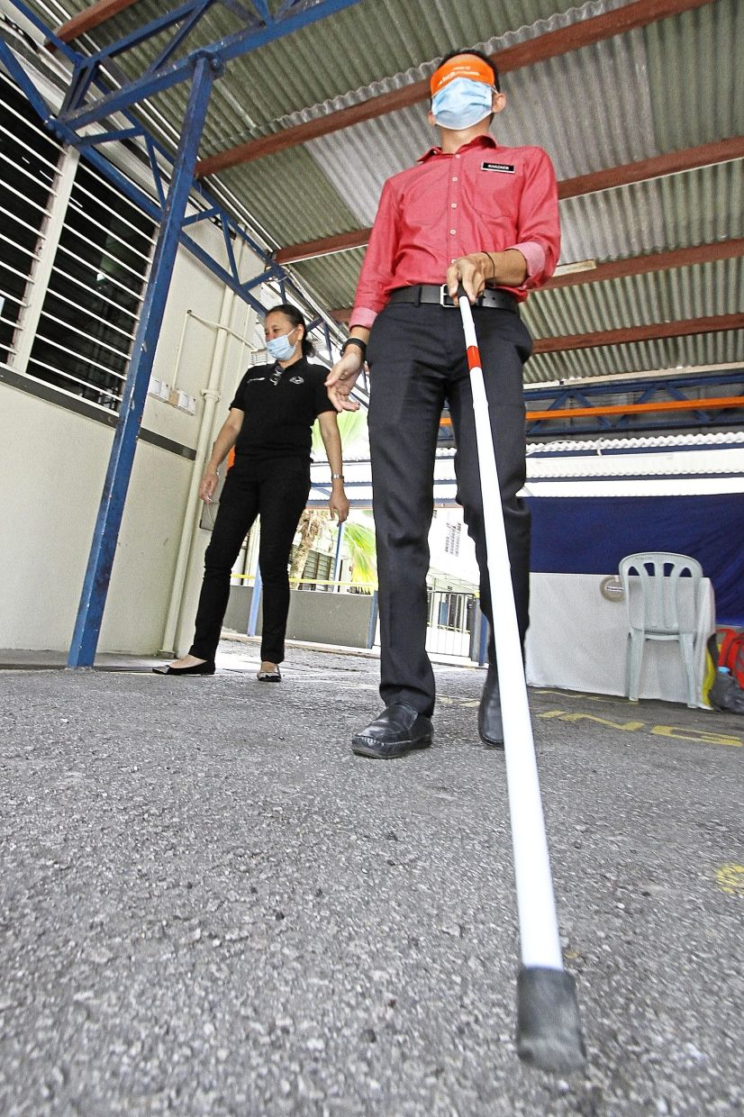 Mohamad Khazaen using a white cane to walk while blindfolded.