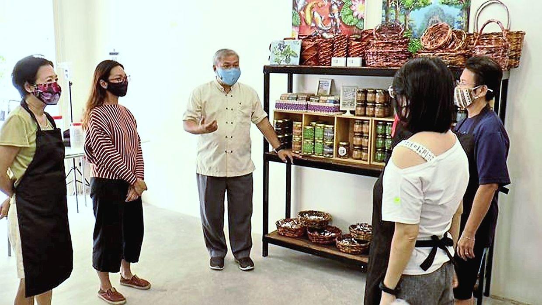 A cup of positivi-tea: Lai (centre) giving visitors a tour of his Seven Tea One social enterprise in Setia Alam.