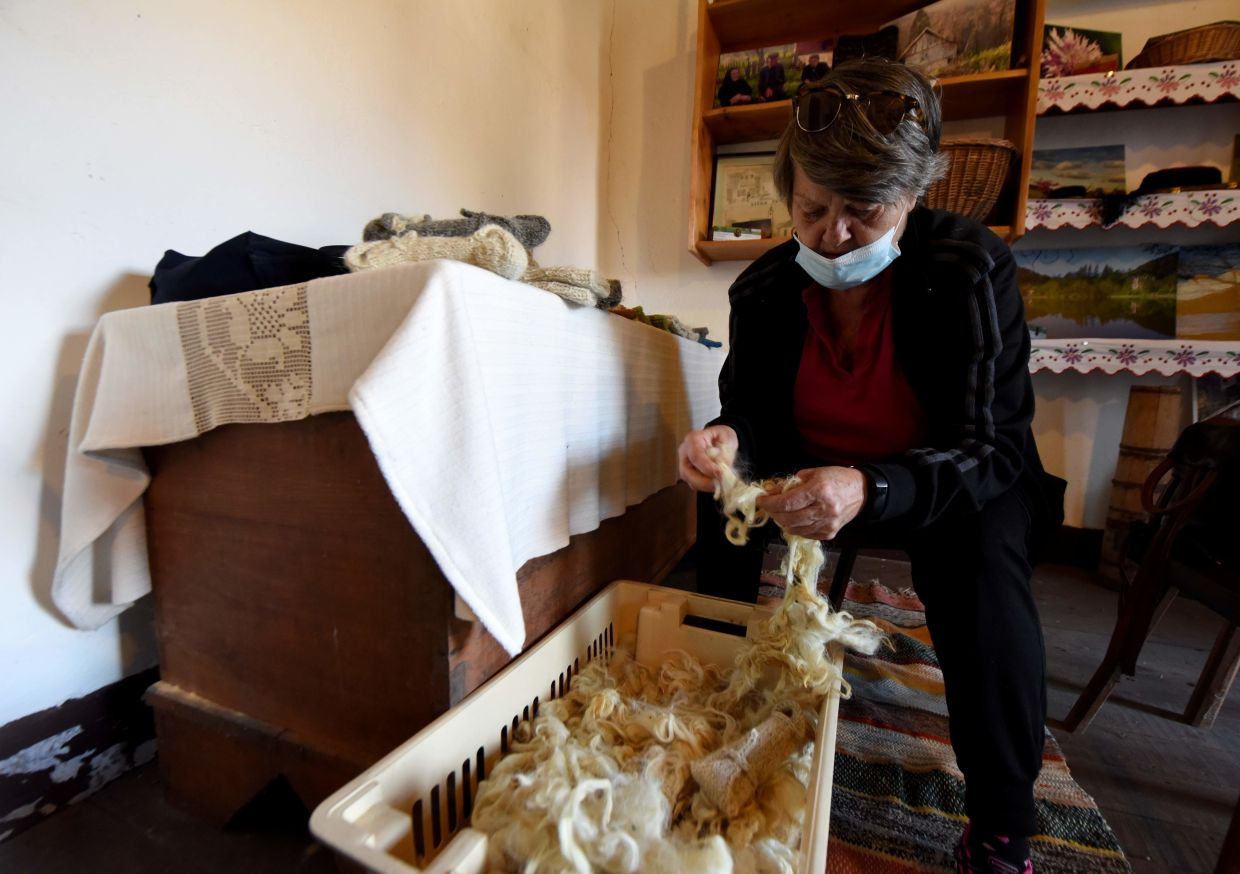 A spread of knitted items including dozens of cylindrical white and grey nakurnjaks, lying on tables in Tara's modest premises, are a sad reminder of the pandemic.