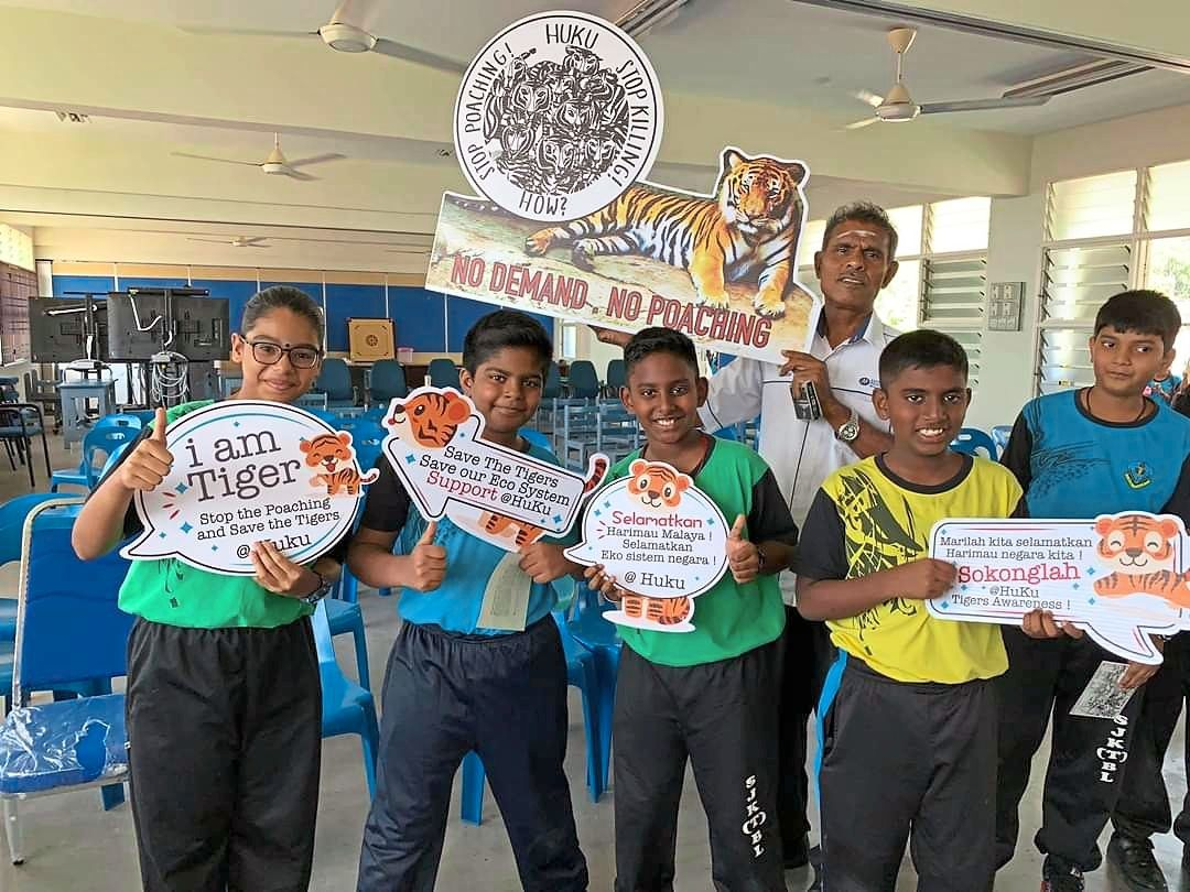 Addressing environmental issues: Sangga and his students posing for a photograph during an awareness campaign to save Malayan tigers.