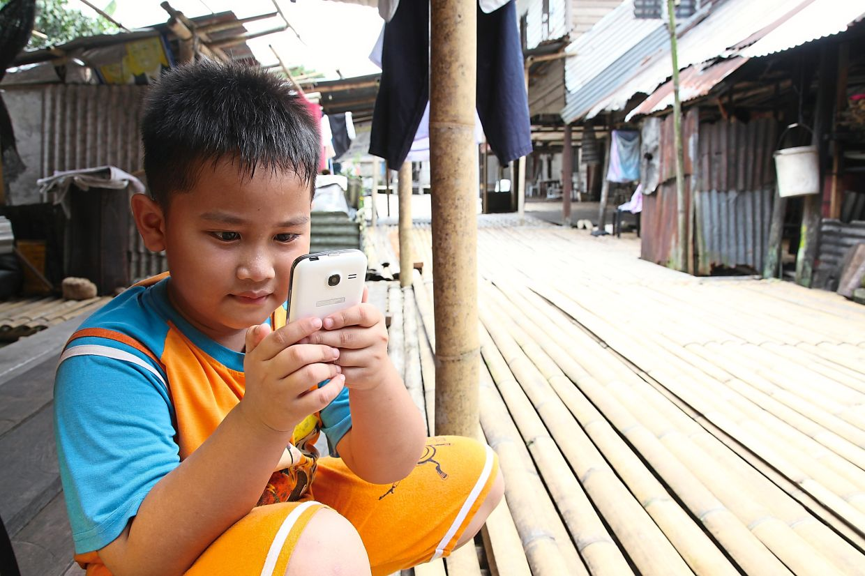 Some children have to share devices with their parents or siblings so their time online is limited. Photo: Unicef