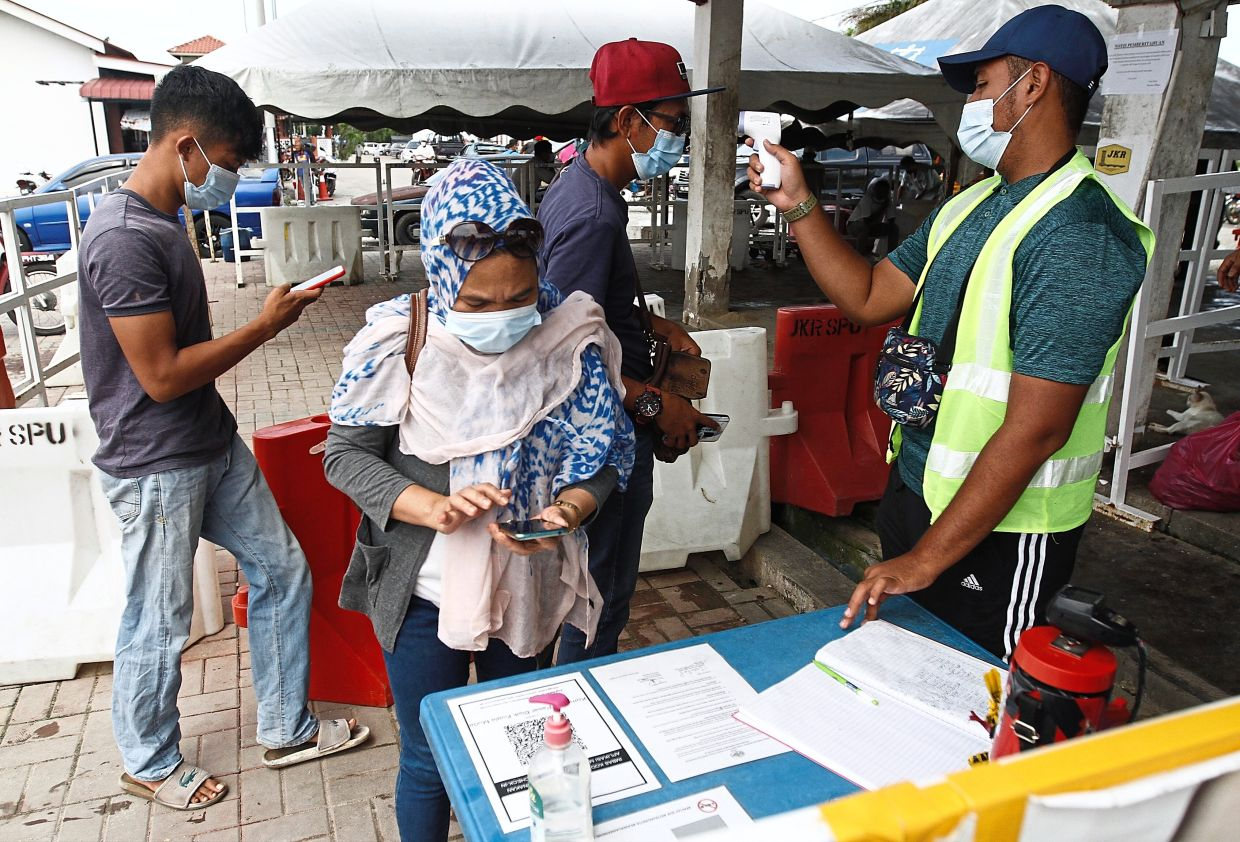 Visitors registering and getting their temperature scanned before being allowed entry into the Whispering Fish Market or Pasar Bisik.
