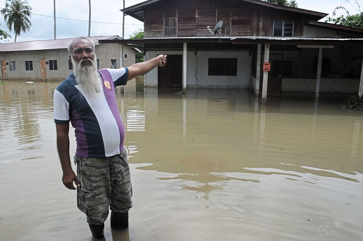 Norizan pointing to his flooded home.