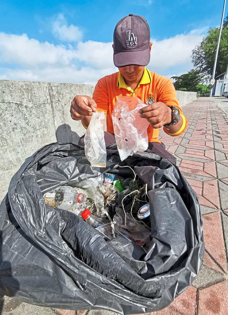 A council cleaner picking up plastic bags still filled with a bit of ketum juice.