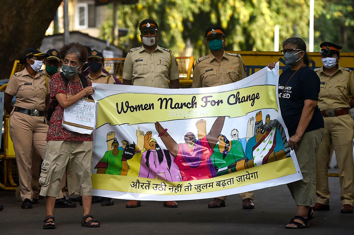 Activists march during a protest to condemn the alleged gang-rape and murder of a 19-year-old woman in Bool Garhi village of Uttar Pradesh state, in Mumbai on October 6. The closure of businesses and schools, as well as cultural and athletic activities, have deprived victims already weakened by economic insecurity of ways to escape violence.