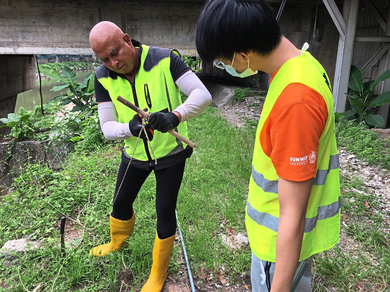 The 'Big Stick' at work: Michael (left) and a young volunteer working to clean up part of the Klang river that flows through Taman Melawati, Selangor.