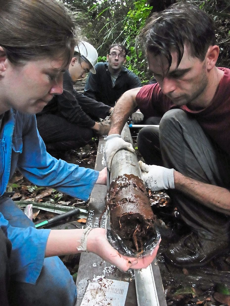 Researchers from the SMART study examining a core sample from a deep layer of peatland. — CHARLES HARVEY
