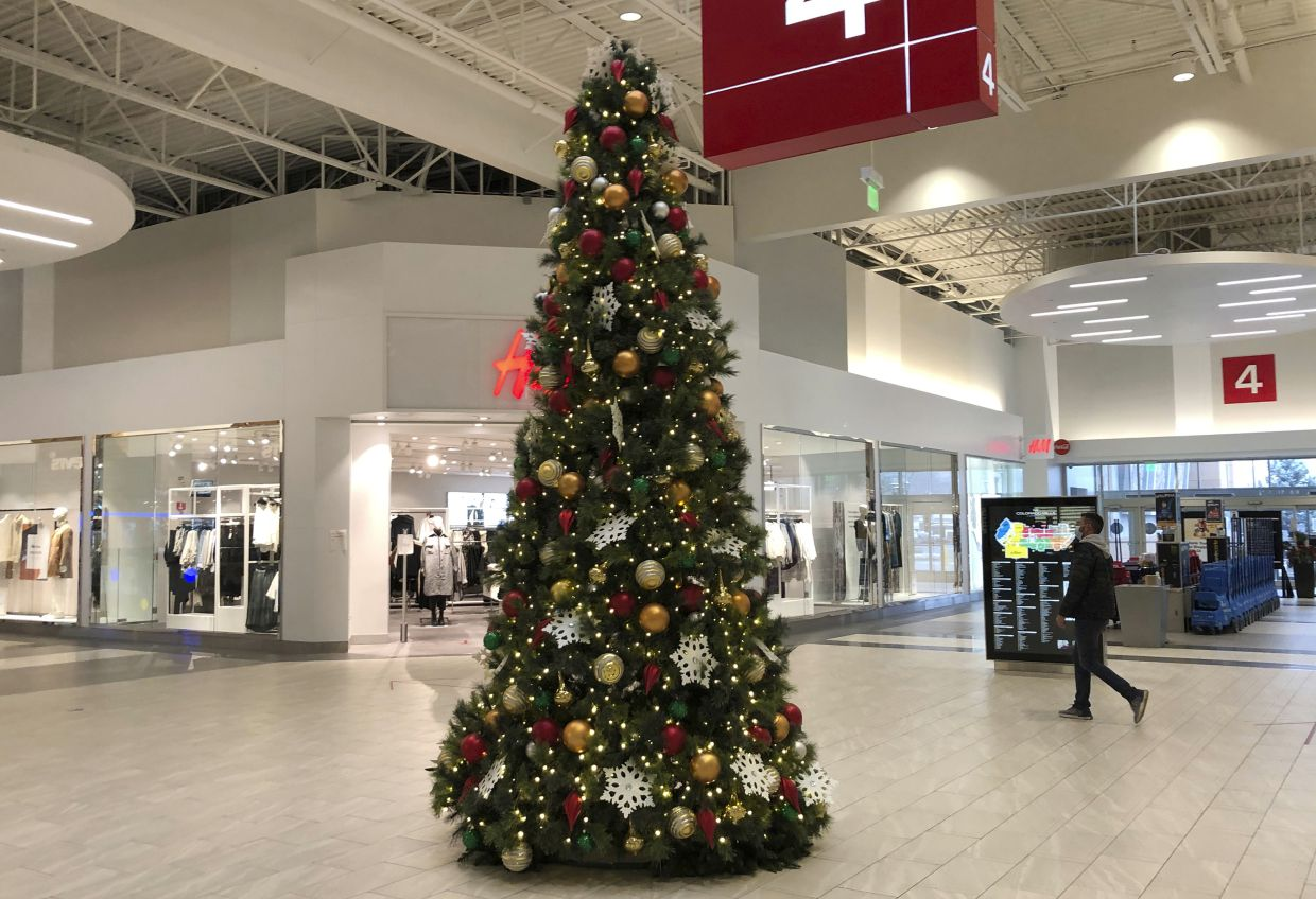 A lone shopper walks past the Christmas tree set up in an outlet mall in Lakewood, Colorado. In normal times, Black Friday is the busiest shopping day of the year, drawing millions of shoppers eager to get started on their holiday spending. But these are not normal times. — AP