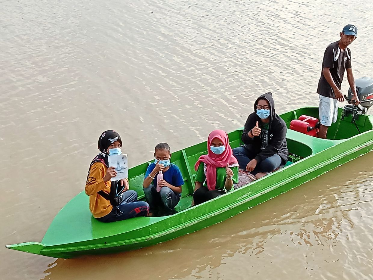 Hartina (second from right) needs to travel 30 minutes by boat to teach the kids on Pulau Mumiang.