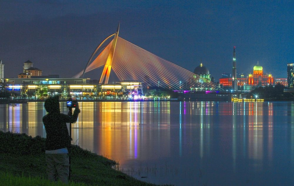 Colourful memory: A visitor snapping a picture of Seri Wawasan Bridge in Putrajaya, illuminated with orange lights in conjunction with World Patient Safety Day 2020 in September. — MOHD SAHAR MISNI/The Star