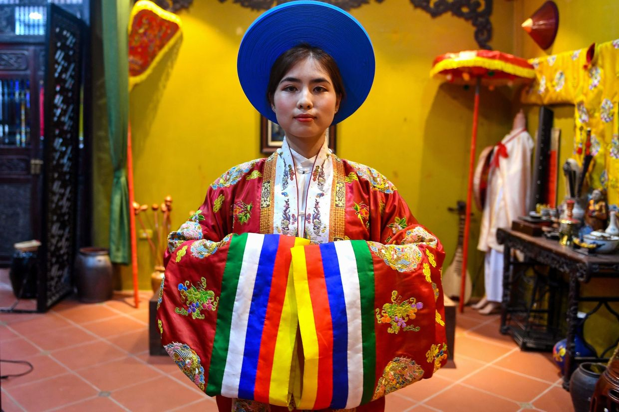 This picture shows student Pham Trang Nhung posing in an outfit based on traditional patterns and styles at the Y Van Hien company studio. Photo: AFP