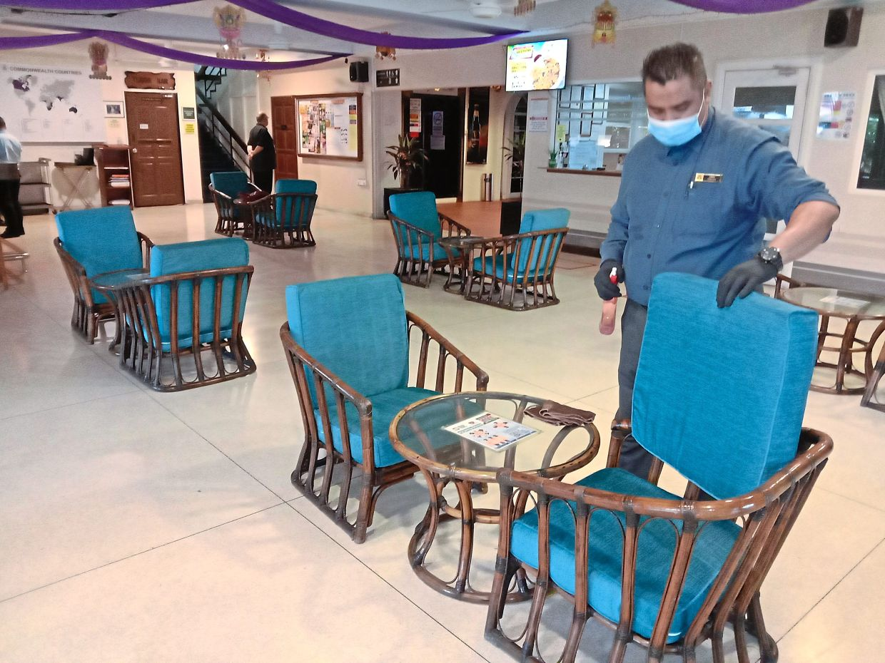At the Commonwealth Club in Bukit Damansara, sofa cushions are sprayed with disinfectant and overturned after a guest leaves.