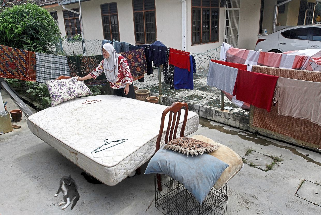 Sakinah drying her mattress and bedsheets outside her house.