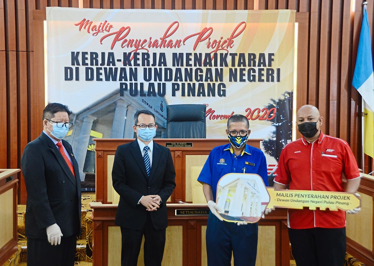 Law (wearing blue tie) with Ahmad Rizal (left) and Roslan (second right) at the building handing over ceremony.