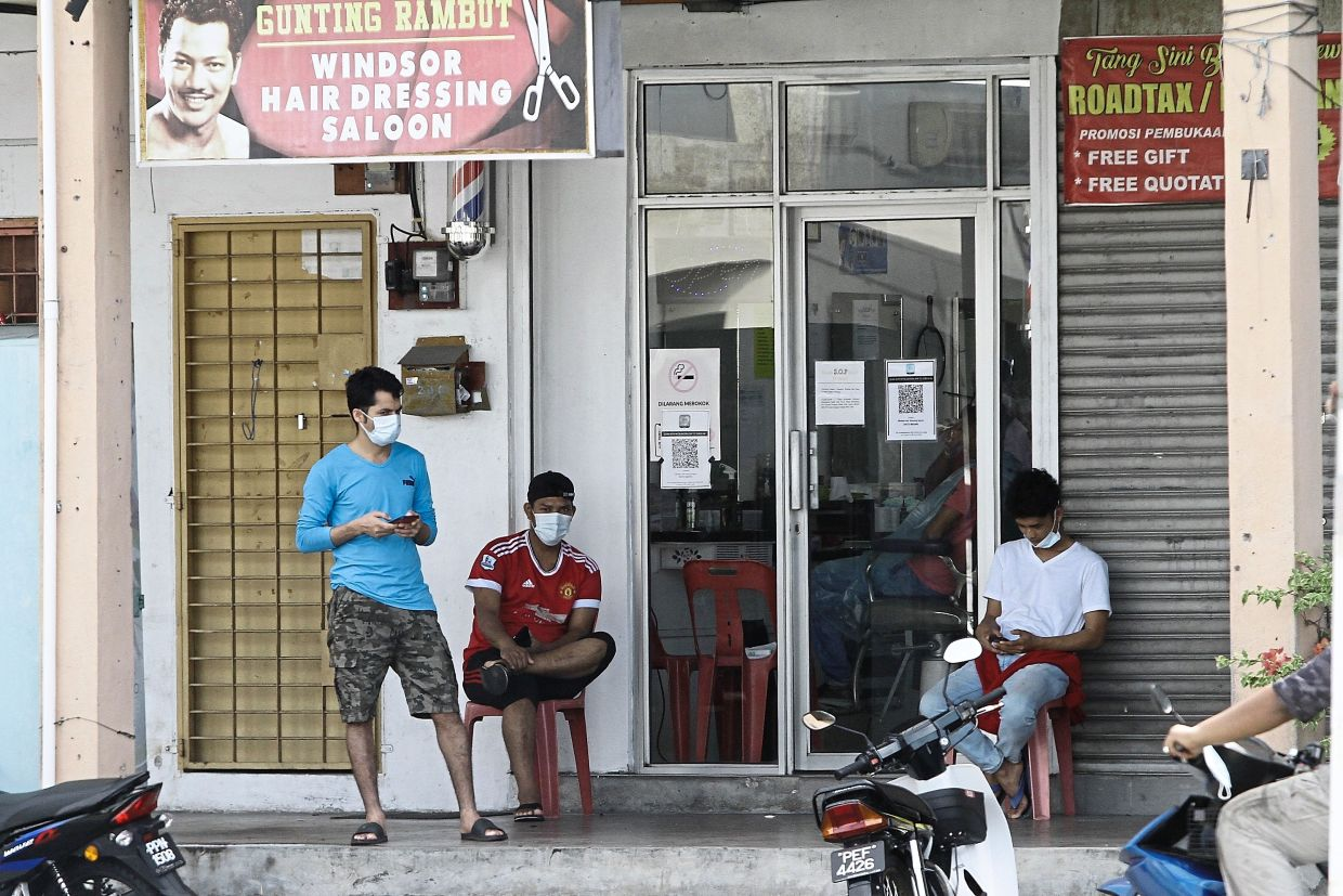 Customers seen waiting outside a barber shop in Jalan Kekabu, Batu Maung.