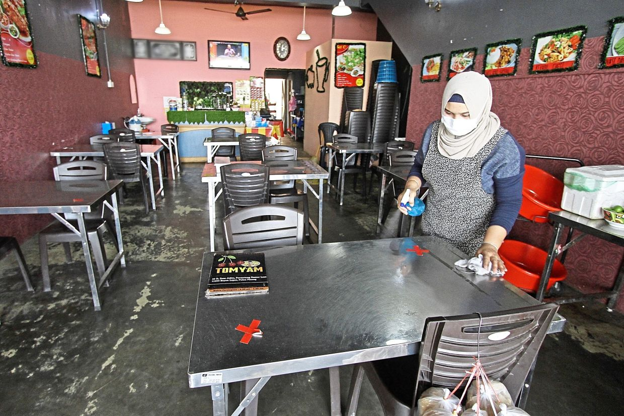 Kak Na sanitising the tables at her eatery in Jalan Kekabu, Batu Maung.