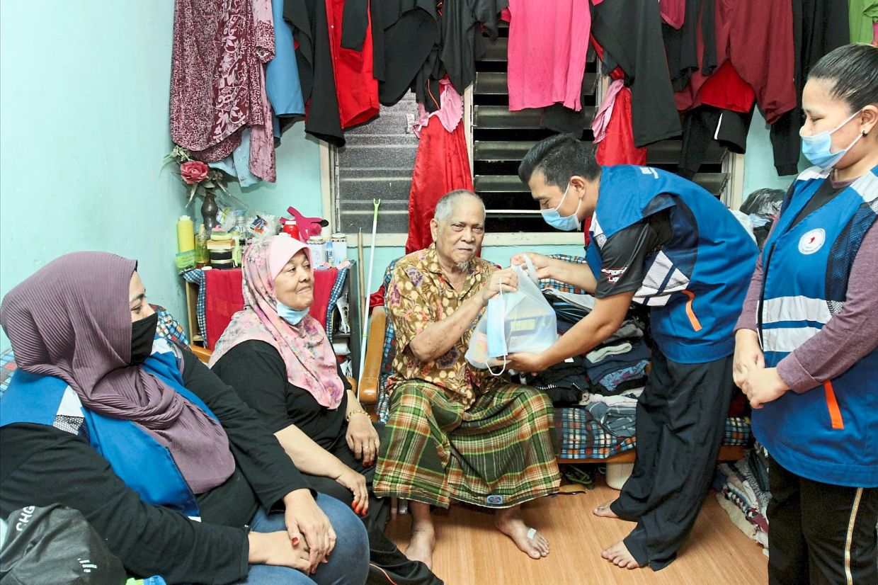Muhammad Saidin (centre) and wife Halijah Mat (second from left) receiving essential items from Mohd Isa (second from right) as volunteers Norlela Abdul (left) and Siti Salwa Abdul Majid look on.