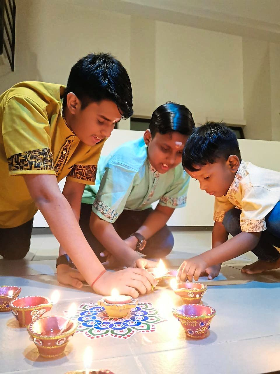 Kanagesvary's sons (from left) T. Kuhan, 13, Arwin, 11, and Kavinesh, three, lighting up agal vilakku at their house entrance.