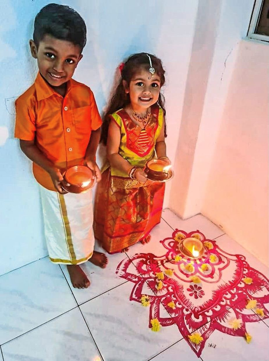 Theehvyan (left) and Thiyassree holding earthen lamps while posing in front of a kolam that they helped their mother draw at their home in Penang.