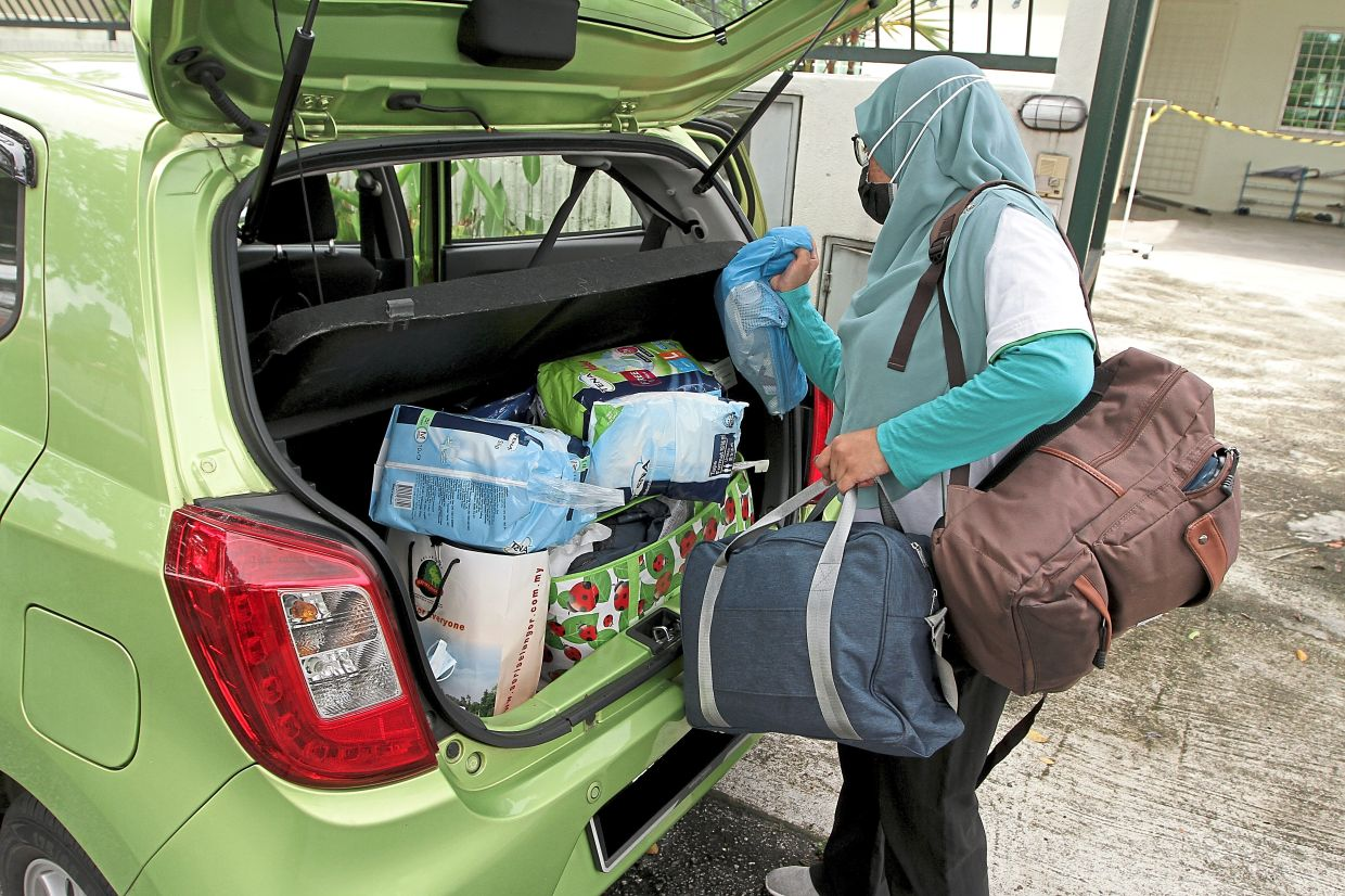 Hospice nurse Nurul Izza loads the supplies for patient visits, into her car. Photo: The Star/Yap Chee Hong