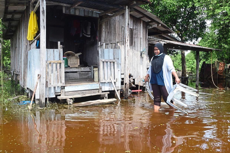 Flood victim Puteri Yasmin Abdul Mubi, 29, wading through the floods near her house in Kampung Padang Garam, near Marang.
