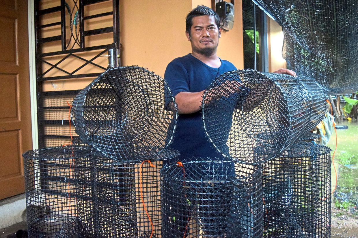 Mechanic Mohamad Sapawi Yunus, 40, showing a bubu (fish trap) that he is selling online via Facebook from his home in Kampung Tok Fakir in Marang. Bubu is a traditional tool used to catch fish in rivers, lakes and swamps.