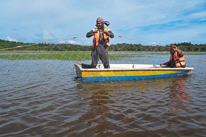 Mohd Suhaimi and his friend Muhd Zukanain Abdullah, 42, inspecting their fishing net in Kampung Durian Pahit, Marang.