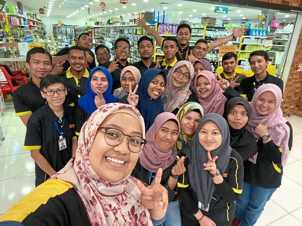 Nabilah (front) with her colleagues at a MR.DIY store. She was a part-time promoter as a student, and since joining fulltime in 2012, she is now division manager in charge of 18 stores and more than 200 employees.
