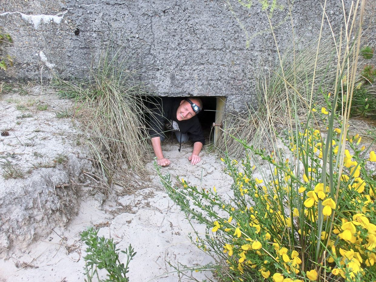 Uwe Stelzmann crawling out of a bunker in western Denmark. He first began geocaching with his family 11 years ago.