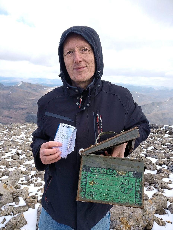 Uwe Stelzmann holding an ammunition box on top of Ben Nevis, the highest point in Scotland.