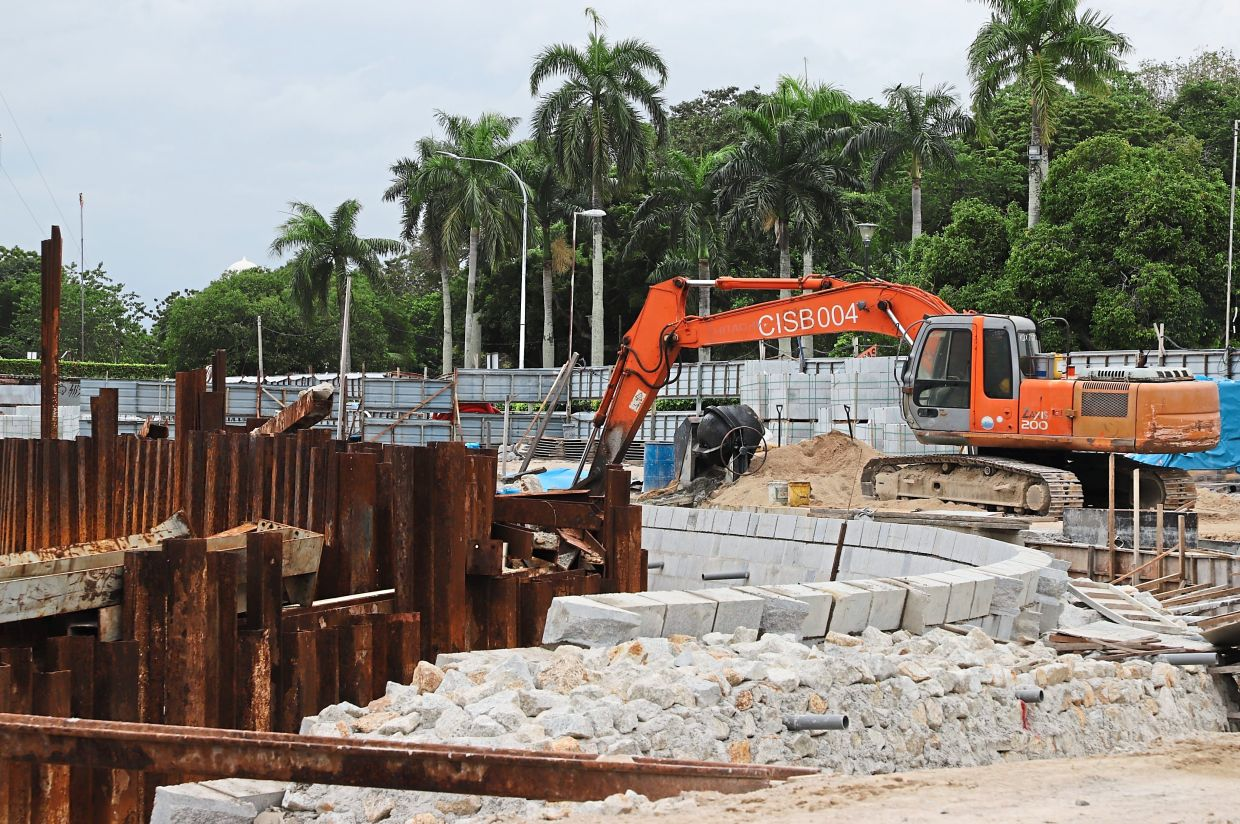 An excavator digging earth at the seawall project site at the Esplanade in George Town.