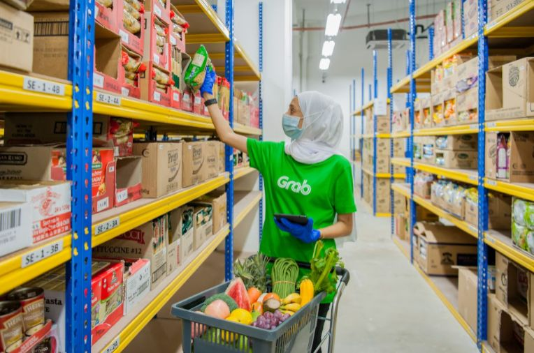 A GrabSupermarket personnel picking out ordered items from its warehouse for delivery to customers.