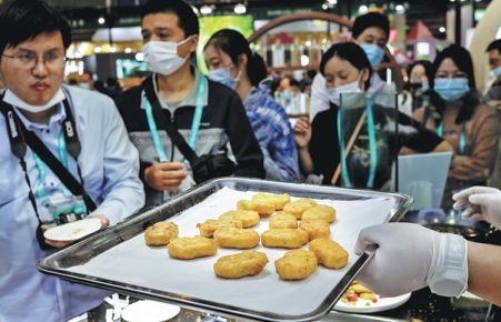 Visitors line up in front of an exhibitor from the United States offering artificial chicken during the third China International Import Expo in Shanghai last month. - CNS-China Daily/Asian News Network