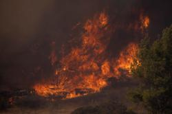 Firefighters battle Southern California canyon blaze against high winds