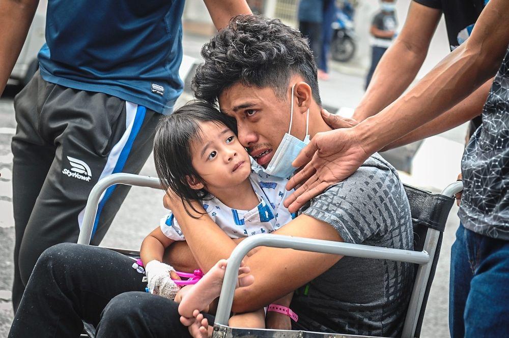 Inconsolable: Syafiq holding his daughter, who was injured in the accident, at the Seberang Jaya Hospital. — Bernama